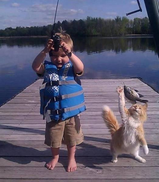 A boy and his cat catching some fish together.