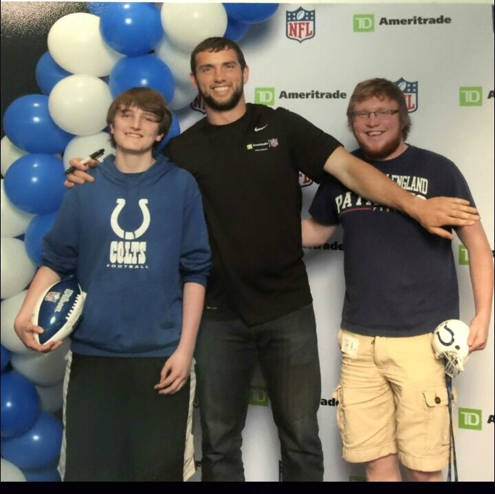 Andrew Luck takes a picture with a Colts fan and a Patriots fan.