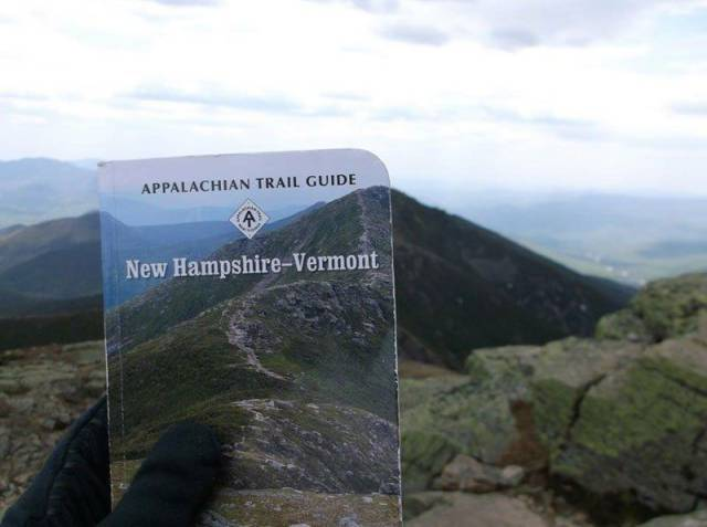 Appalachian Trail Guide held up at the exact location the cover picture was taken.