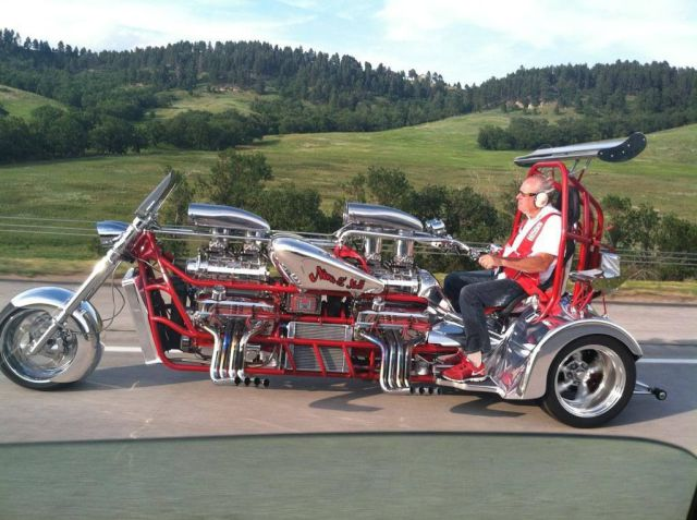 Extended trike with two blown V-8 engines, wheelie bar, dual rear wings, roll bar, and he doesn't even buy matching ear muffs.