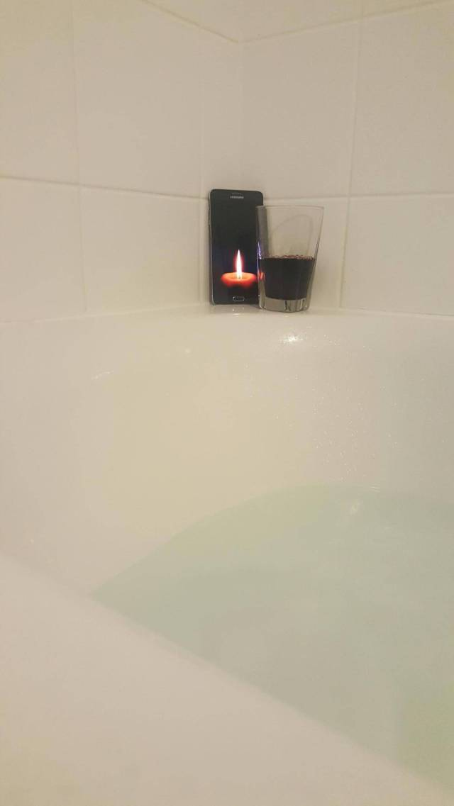 Relaxing bubble bath with a glass of wine and a candle.