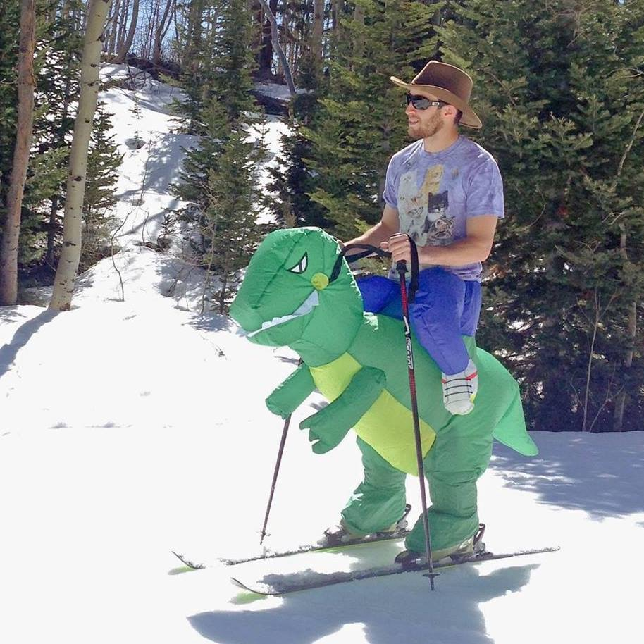 Snow skiing on the back of a Tyrannosaurus Rex.