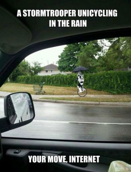 Stormtrooper riding a unicycle in the rain.