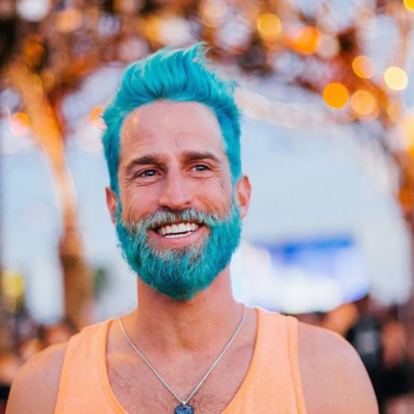 There is a new fad happening where men dye their hair and beards vibrant colors. This guy is going for the Smurf look.