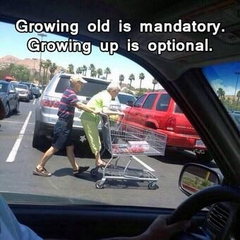 An older couple having some fun on a trip to the store by riding on the cart like everyone did as a child.