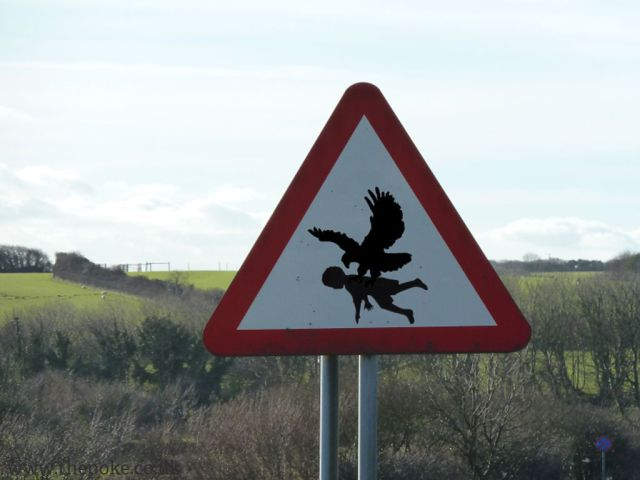 This large birds snatching up children warning sign is creepy.