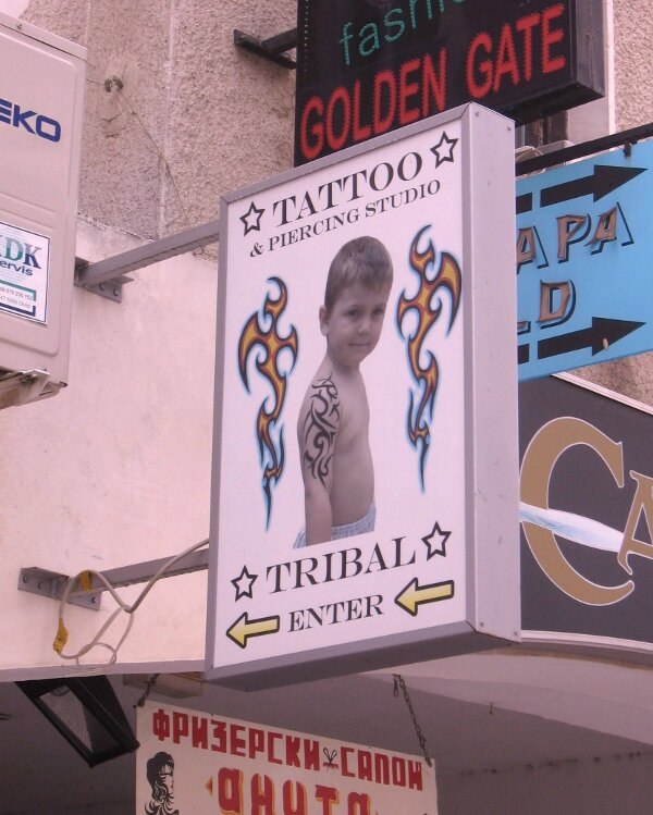 This tattoo shop sign with a kid showing off his tribal tattoo might make you say WTF!