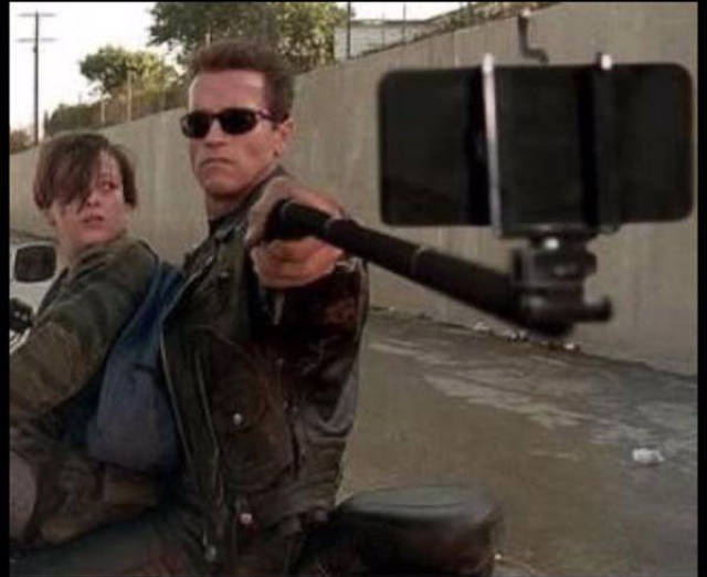 Vintage behind the scenes photo of Arnold Schwarzenegger taking a selfie in the movie Terminator 2: Judgement Day.